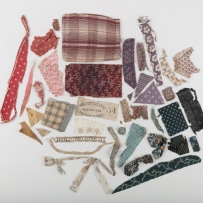 A grouping of fabric scraps of different colours, sizes and shapes against white background.
