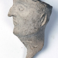 Profile view of clay pipe carved into man's head with beak-shaped nose.