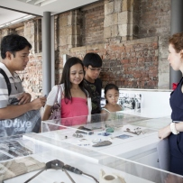 Family of two adults and two children talking to woman with ponytail while looking into display case.