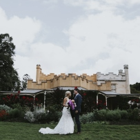 Couple in wedding outfits on lawn in front of house and fountain.