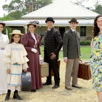 Group of people dressed in period costume with woman to right in contemporary clothes.