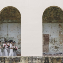 Wedding party behind archways.