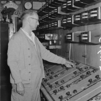 Man operating bank of switches.