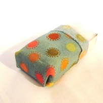 Matchbox toy bed covered with patterned fabric.