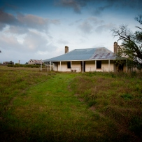 Old farmhouse with atmospheric sky above.