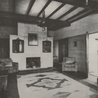 Black and white interior shot of room with exposed ceiling beams.