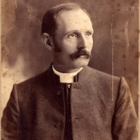 Sepia toned photo of moustached man with white collar and dark jacket.