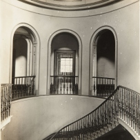 B/w view of eliptical staircase with handrials leading to upper stair balcony with 3 tall arches, each with railings.