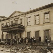 B/w photo of a large group of people standing in front of Elizabeth Bay House, with roadworks underway in front of the building.