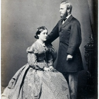Woman in full skirted dress, seated, with man wearing three quarter length coat, standing to her left.