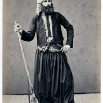 Sepia toned carte de visite portrait of unidentified man standing facing the camera with his left hand raised to his waist and his other hand holding a long gun, wearing a turban, full beard, striped and decoratively trimmed high shoes.
