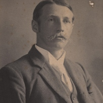 Black and white photo of moustached man.