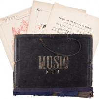 Leather book with word Music on cover, with sheet music underneath.