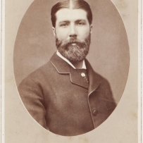 gelatin paper print, sepia toned portrait photograph of man. He wears a dark coloured suit with a collar and cravat. A pin is attached to his cravat. He has a full beard.