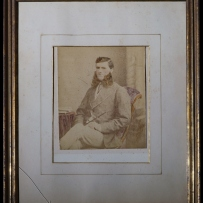 A framed albumen print photograph of a man. Full length portrait, sitting on easy chair, half facing camera L, legs crossed, both hands resting on lap, the R holding a riding crop.