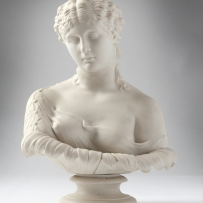 White bust of young woman on pedestal, one shoulder bare, the other draped.