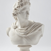 White bust of man wearing wreath in hair and drapery around neck, on pedestal.