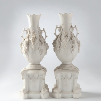 Shaped pedestal base with corners decorated with scrolls to the foot and ram's heads to the upper edge liked by applied swags; the vase with circular flaring foot, ovoid body and long, narrow neck, rim with pointed edge. Pair of handles in the form of bra