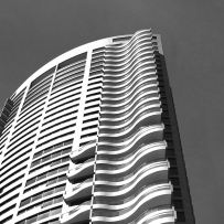 Black and white image, looking up at exterior of tall building.