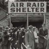 Black and white photo of people coming out of underground, with sign above that reads 'AIR RAID SHELTER'.