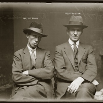 Black and white photograph of twoseated men dressed in hats and suits looking quite defiantly at the camera.