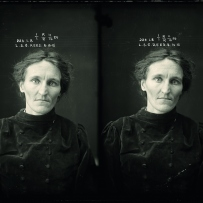 Police photograph of older lady with grey hair. She wears a black velvet jacket buttoned to her neck.