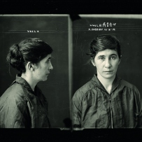 Police photograph of women showing front and side. She has long dark hair tied in a bun and wears a dark cloth coat.