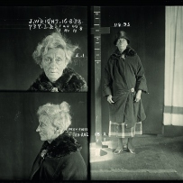 Police photograph of an old lady with messy grey hair piled on her head wearing a black coat and hat..