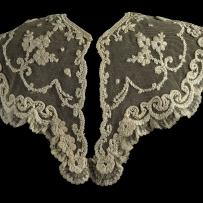 A lace collar on a black background which appears to have floral motifs raised up by the insertion of cord