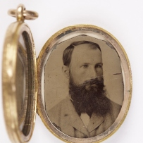 Handcoloured portrait tintype photograph of bearded man. Photograph sits within small oval gold locket, hinged at one side and attached with gold ring at top.