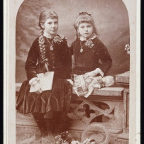 Sepia toned photo of two girls seated.