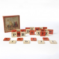 This is a colour photograph of a small wooden box with a colour graphic on top and containing red and white wooden tiles with individual black letters