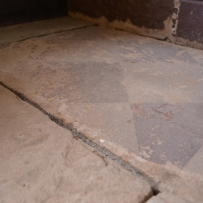 Closeup of sandstone flagstones showing faint black & white painted surface.