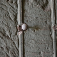 Closeup of small picture hook hammered into wall.