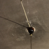Ceiling with light fitting surrounded by smoke stains from earlier lighting such as candles and lamps.
