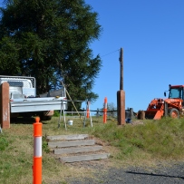 Original driveway access showing wooden steps and old posts, with ute and earthmover parked in background.