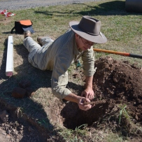 Man lying on front over hole, supported on elbow, with rusted metal object in his hand.