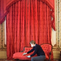 Person kneeling in front of red furniture and drapes.
