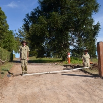 Two men standing on driveway, one down in old gatepost hole, with level on ground to show distance between them.