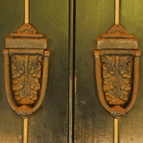 Twin door knockers on wooden door, closeup.