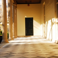 Sunlit porch area, with line of columns to left, leading up to doorway in background.