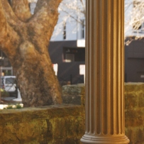 View of column base with low stone wall and tree behind, with streetscape in background.