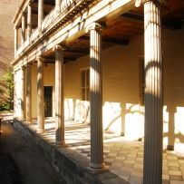 Exterior of two storey building, with columns, sunlit porch area and verandah above.
