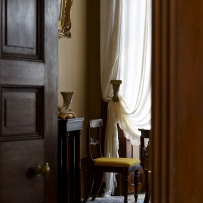 Partial glimpse of room through half open doorway, showing yellow covered chairs, sheer fabric curtains and large window, along with ornaments and picture frame.