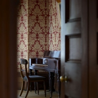 Glimpse through half open door to view a chair and piano against highly patterned pink and red wallpaper