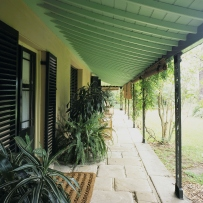 Colour photo of verandah showing flagstone floor tiles, door mats, potted plants and cane chairs, facing the lawn and garden.