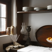 timber shelves and household items photographed against soft powdery distempered walls