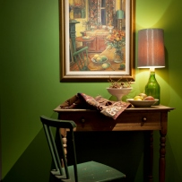 Shot of chair, desk and lamp against green wall with painting above.