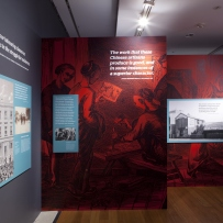This is a photo of red painted wall with a graphic printed over the top and text panels hanging from the wall