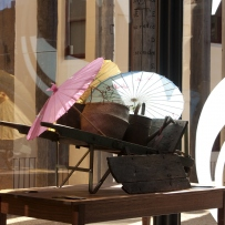 This is a photograph of three Chinese style parasols on a wheelbarrow in the entry to the Museum of Sydney